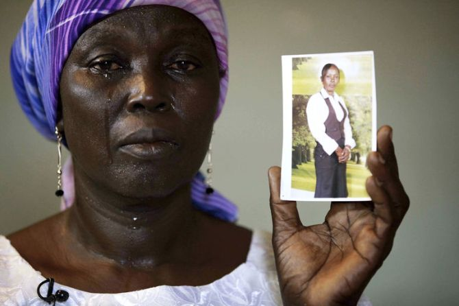 Martha Mark, the mother of one of the kidnapped school girls cries as she displays her photo, in the family house, in Chibok, Nigeria, May 19, 2014.